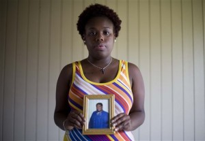 "Najee Washington holds a photo of her grandmother Ethel Lance, one of the nine people killed in Wednesday's shooting at Emanuel AME Church, as she poses for a portrait outside her home Friday, June 19, 2015, in Charleston, S.C. ""She cared for everyone. She took care of people. She would give her last to anyone,"" said Washington. ""That's what she was and that's what she'll always be."" (AP Photo/David Goldman)"